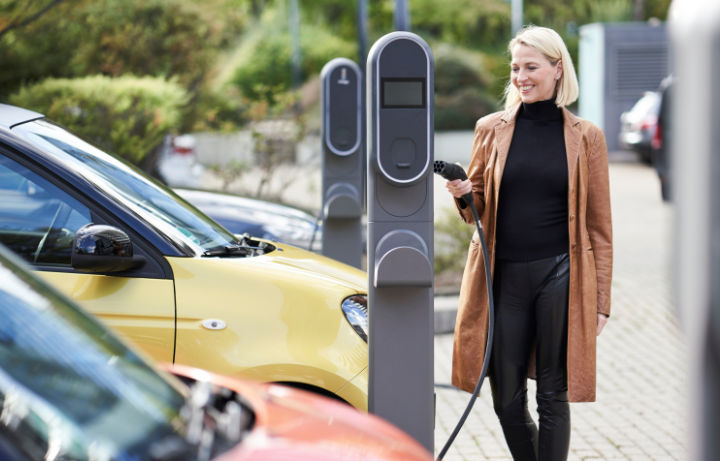 A photo of a young woman connecting her vehicle to an office car park EV charger